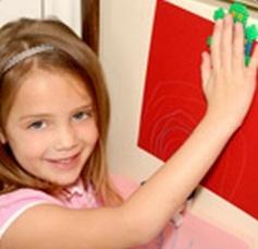 Dziewczynka maluje magnesy na lodówkę